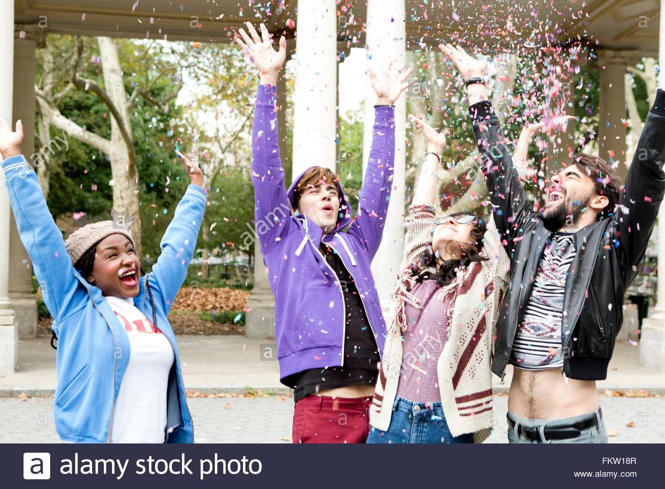 Young hipster couples throwing confetti in park - Stock Image