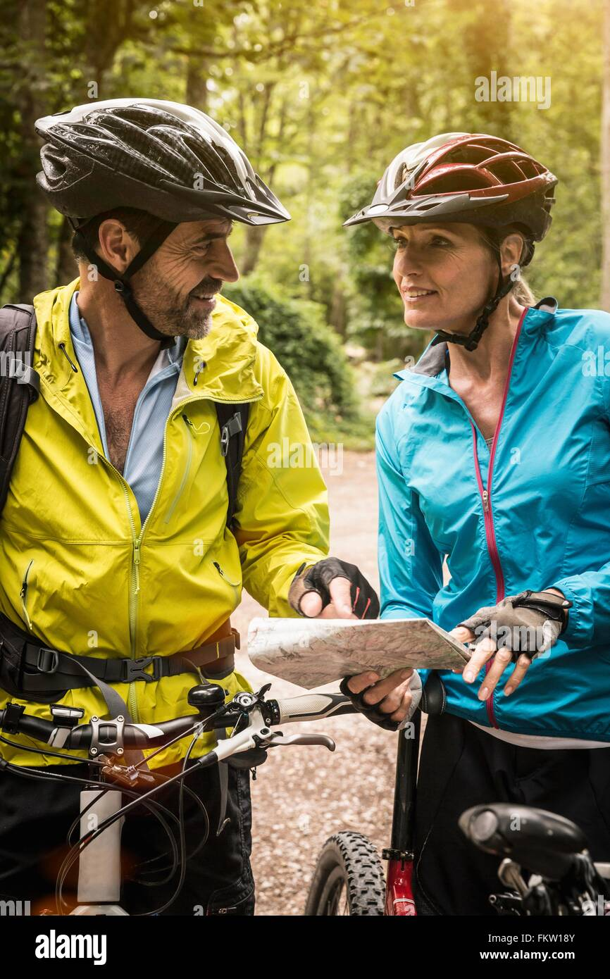 Mature mountain biking couple checking map in forest - Stock Image