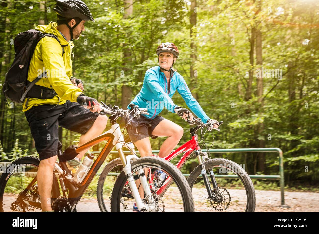 Mature mountain biking couple chatting and cycling along rural forest road - Stock Image