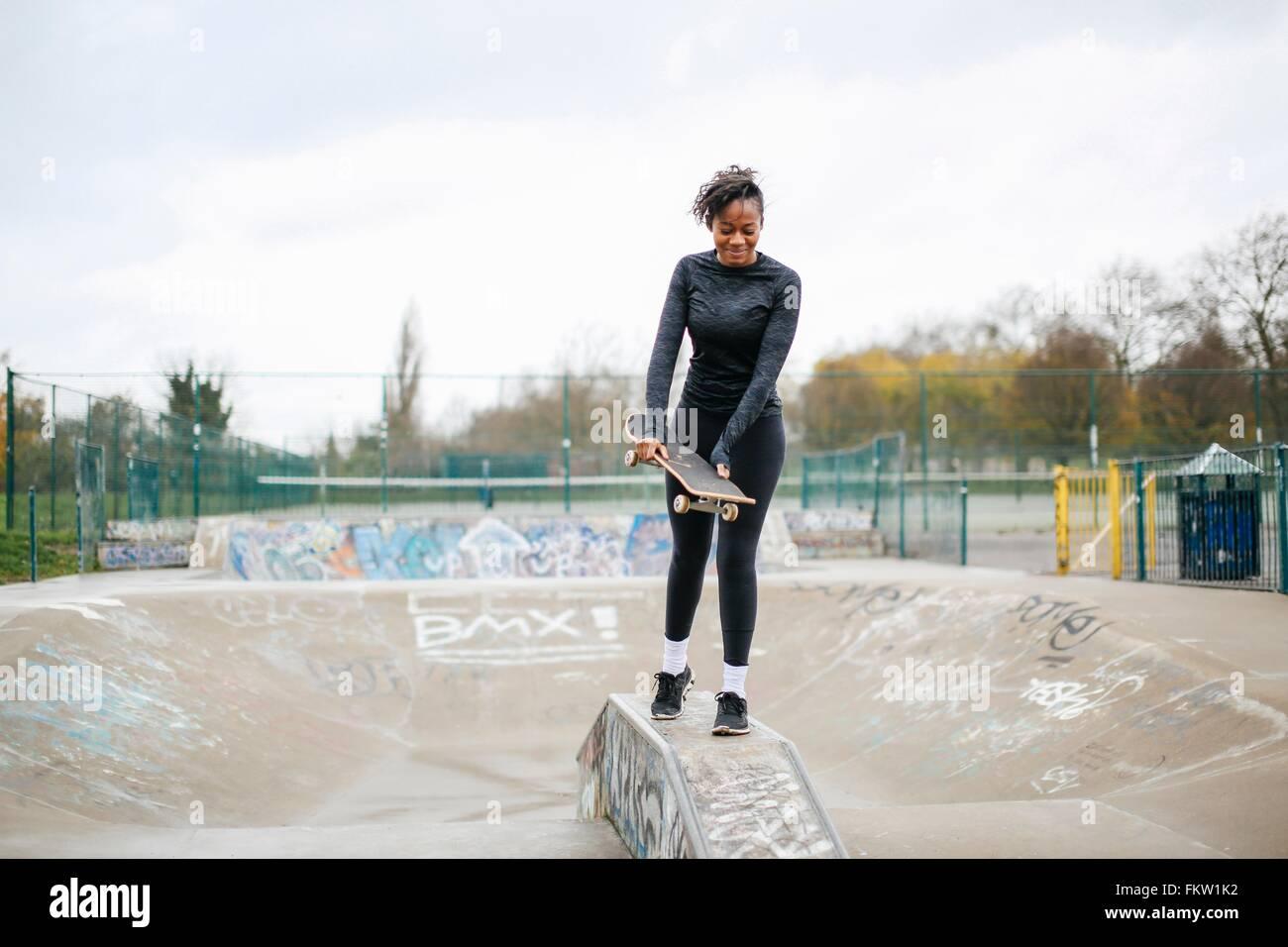 Young female skateboarder preparing to practice in skateboard park - Stock Image