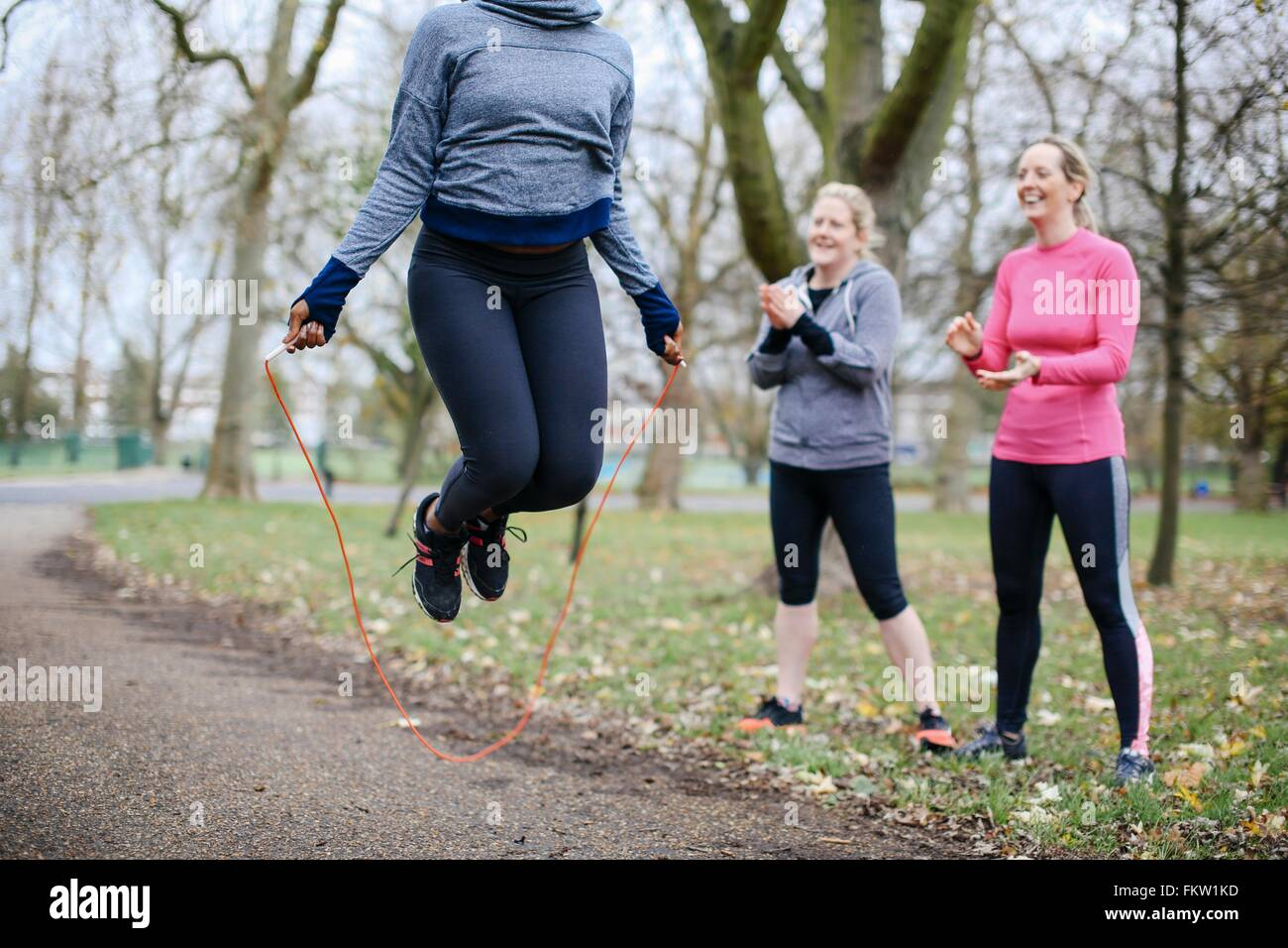 Cropped view of young woman and friends training with skipping rope in park - Stock Image