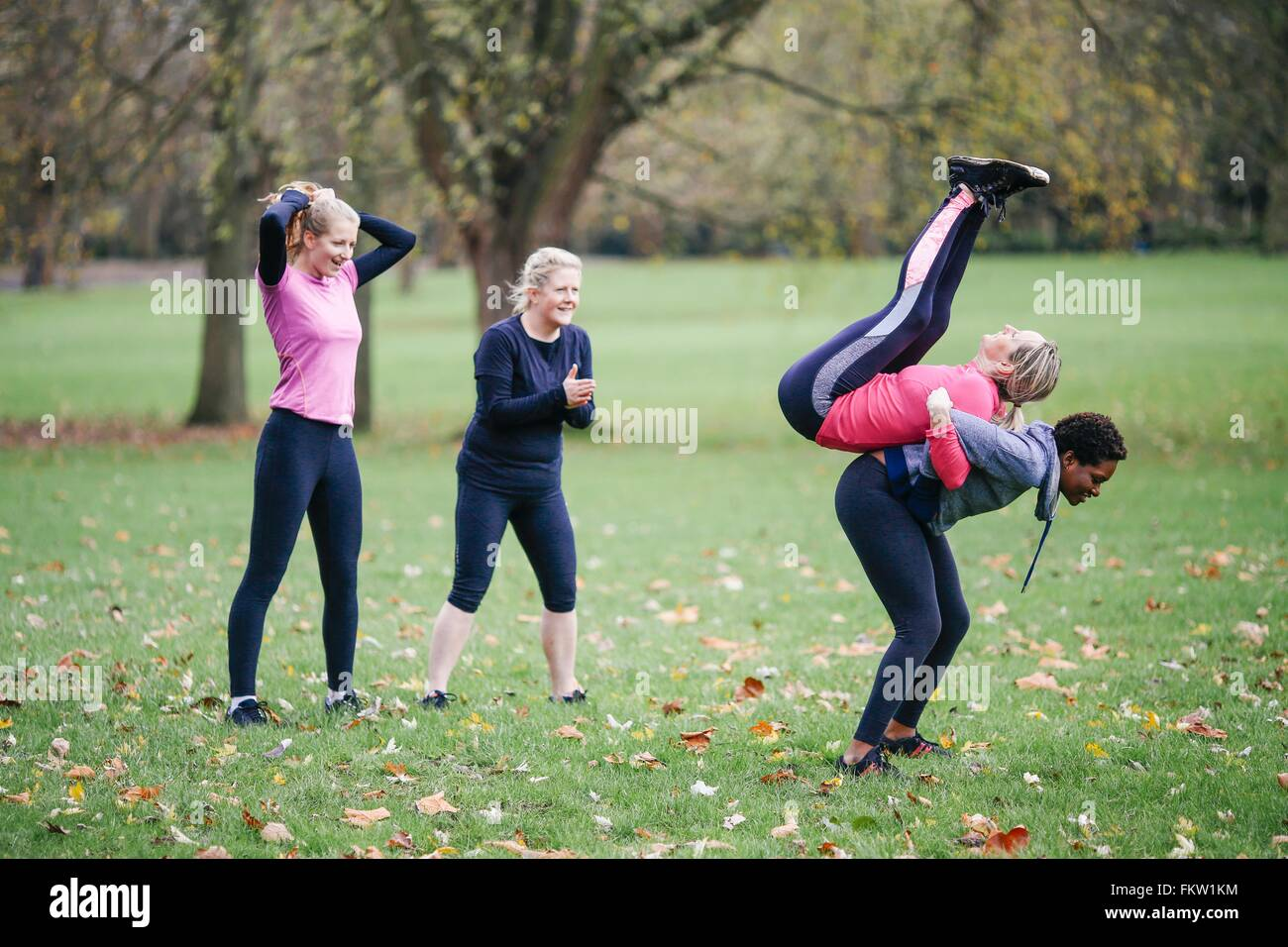 Women and teenager doing warm up exercises in park - Stock Image