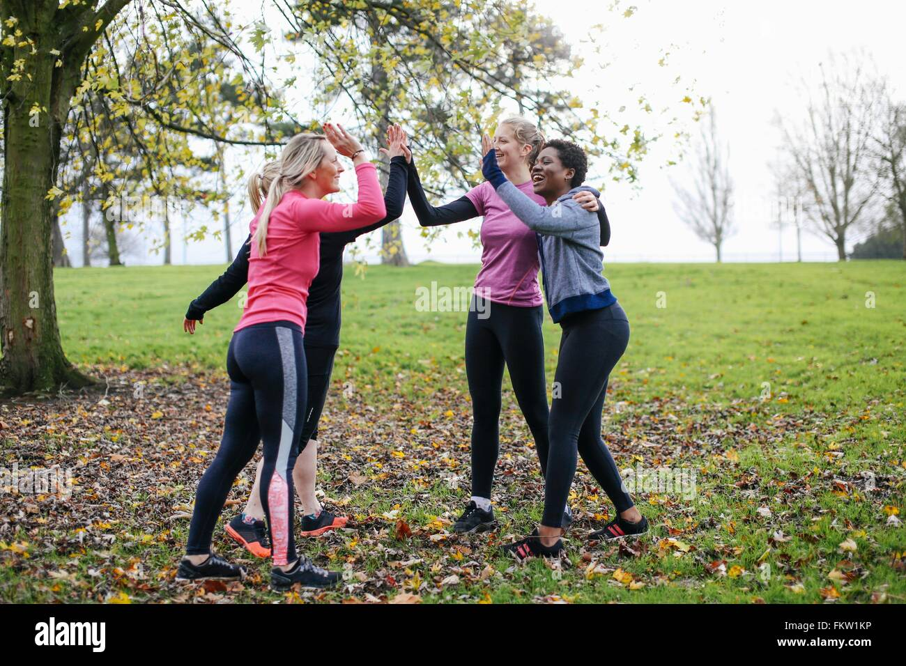 Women and teenager preparing to train giving each other a high five in park - Stock Image