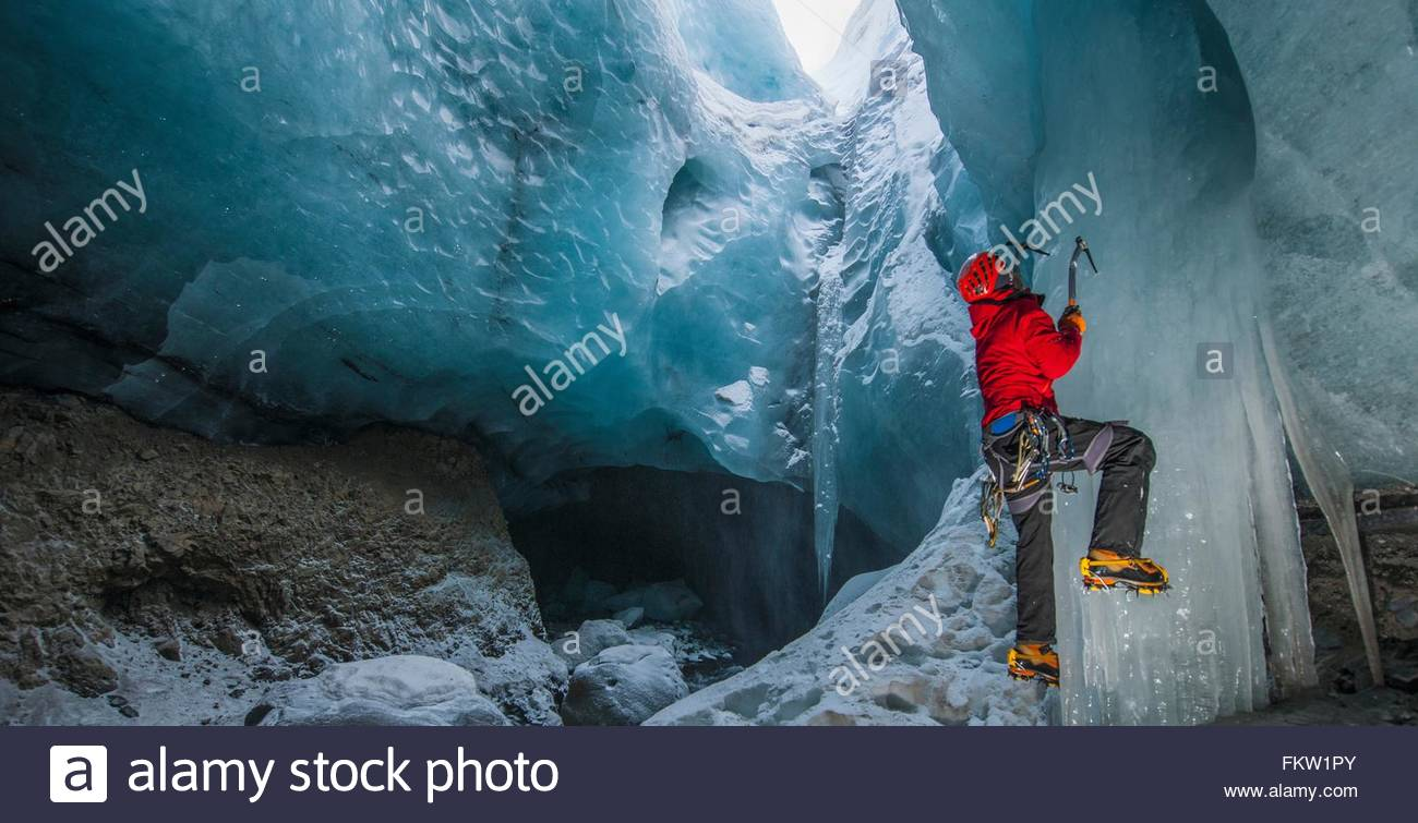 Ice climber climbing up ice cave below the Gigjokull glacier, Thorsmork, Iceland - Stock Image