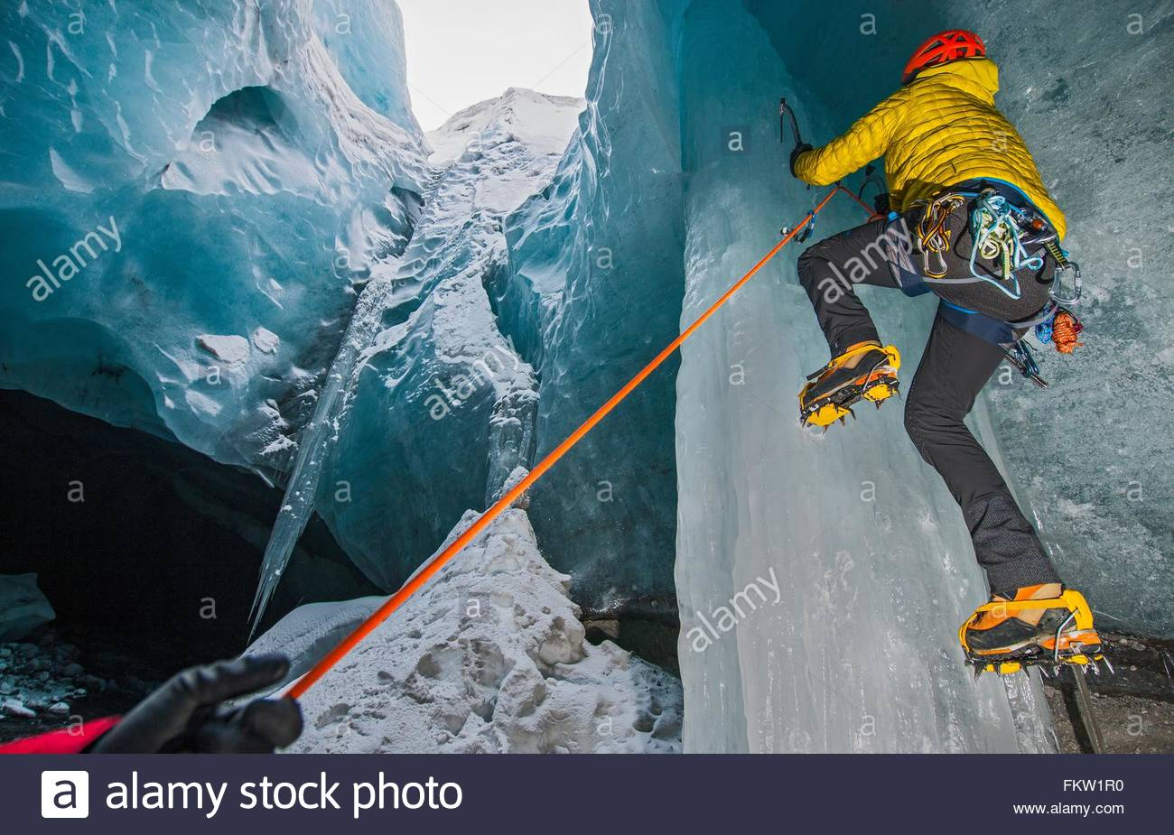 Ice climbers climbing up ice cave below the Gigjokull glacier, Thorsmork, Iceland - Stock Image