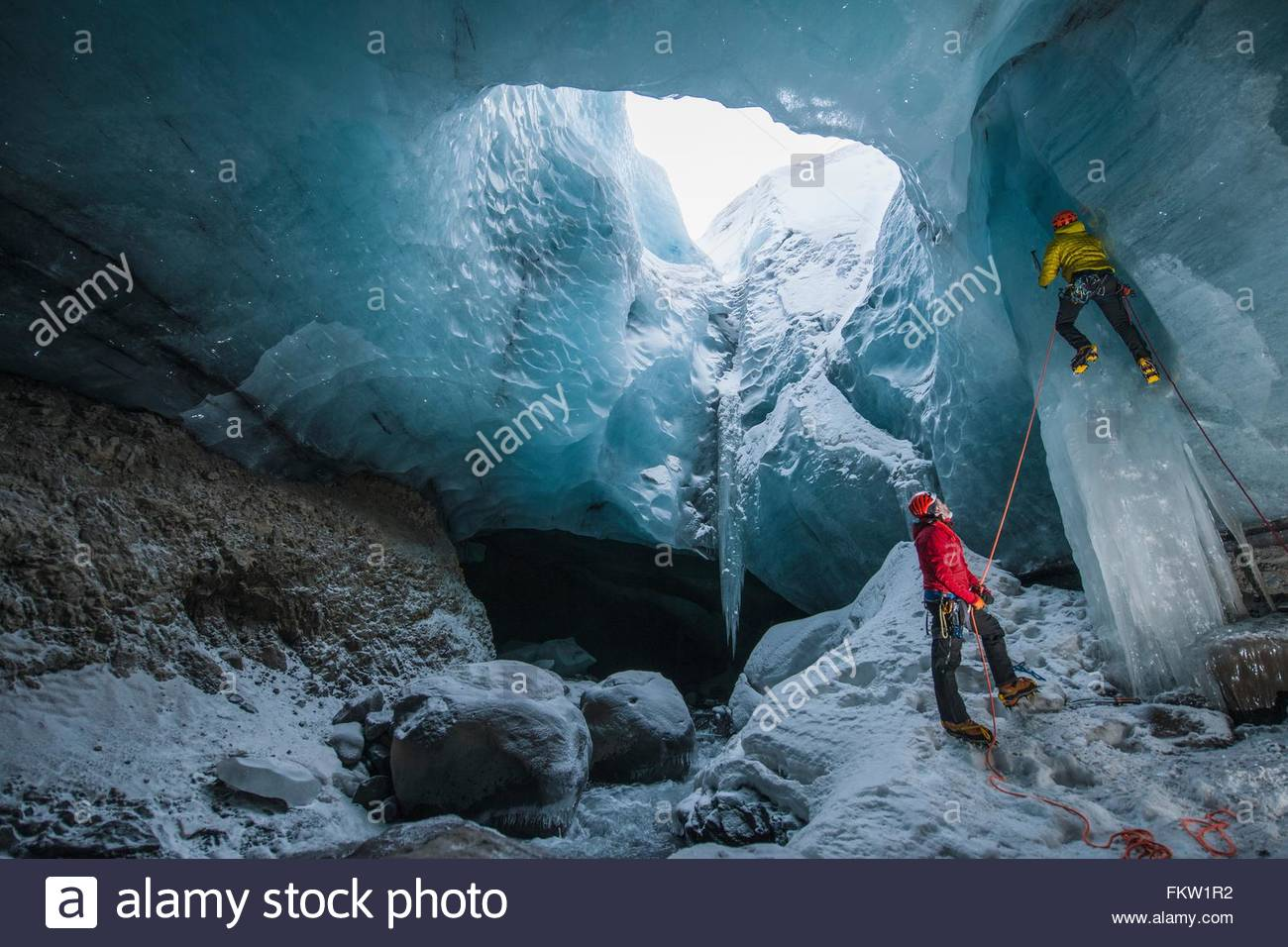 Two ice climbers climbing up ice cave below the Gigjokull glacier, Thorsmork, Iceland - Stock Image