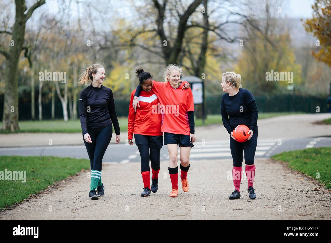 Female soccer players en route to play soccer in park - Stock Image