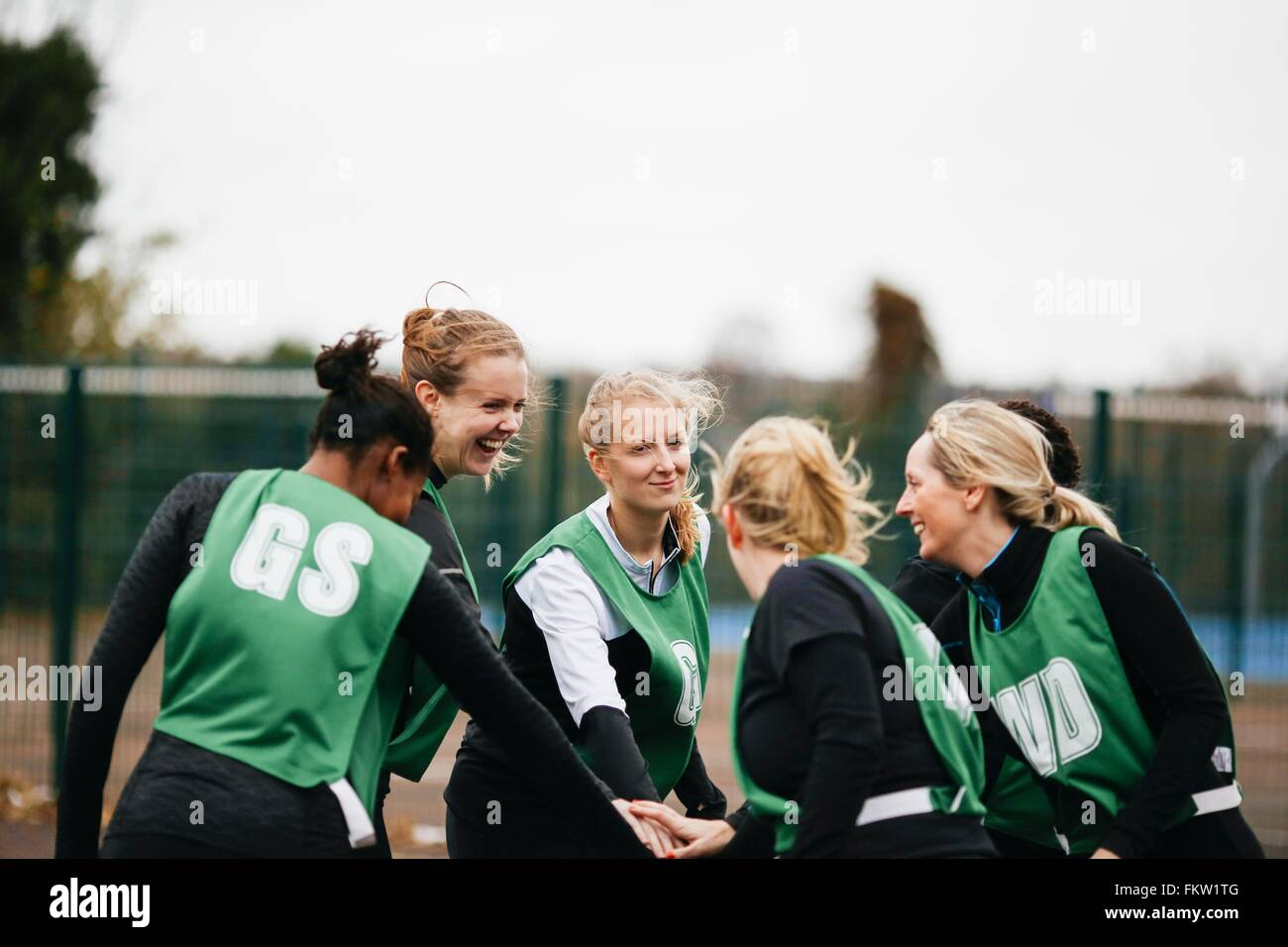 Female netball team shaking hands on netball court - Stock Image