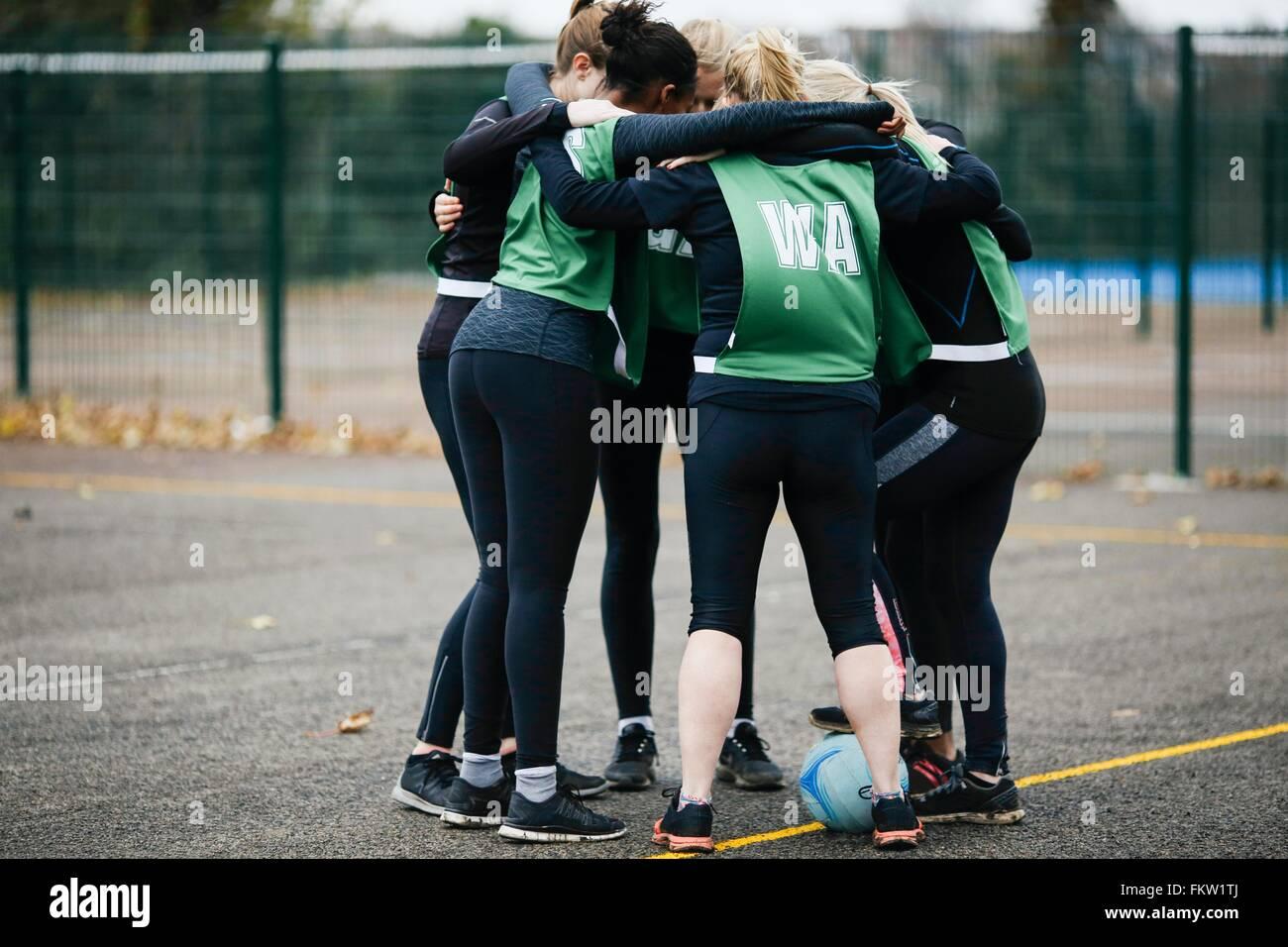 Female netball team in planning huddle on netball court - Stock Image