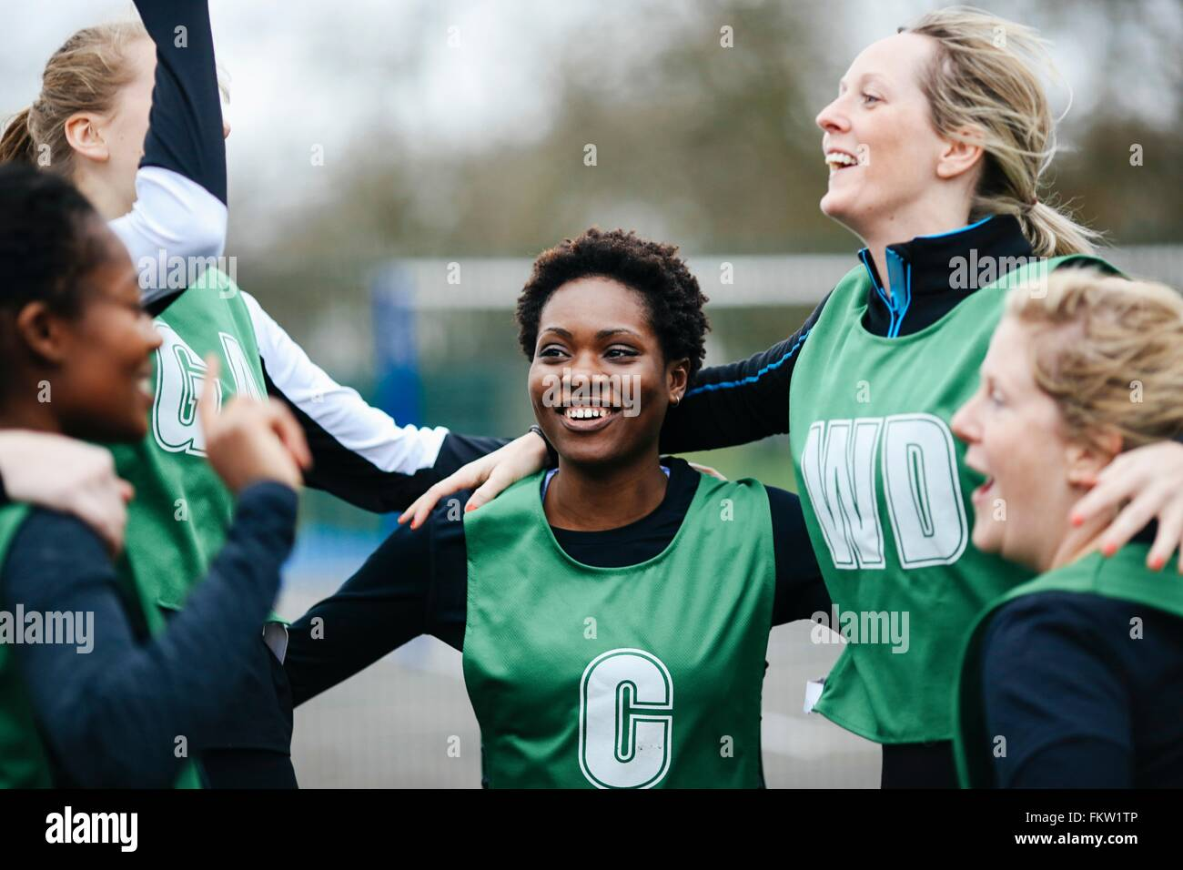 Female netball team celebrating win on netball court - Stock Image