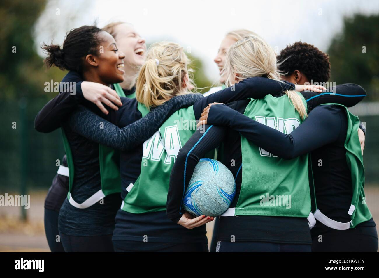 Female netball team celebrating in huddle on netball court - Stock Image