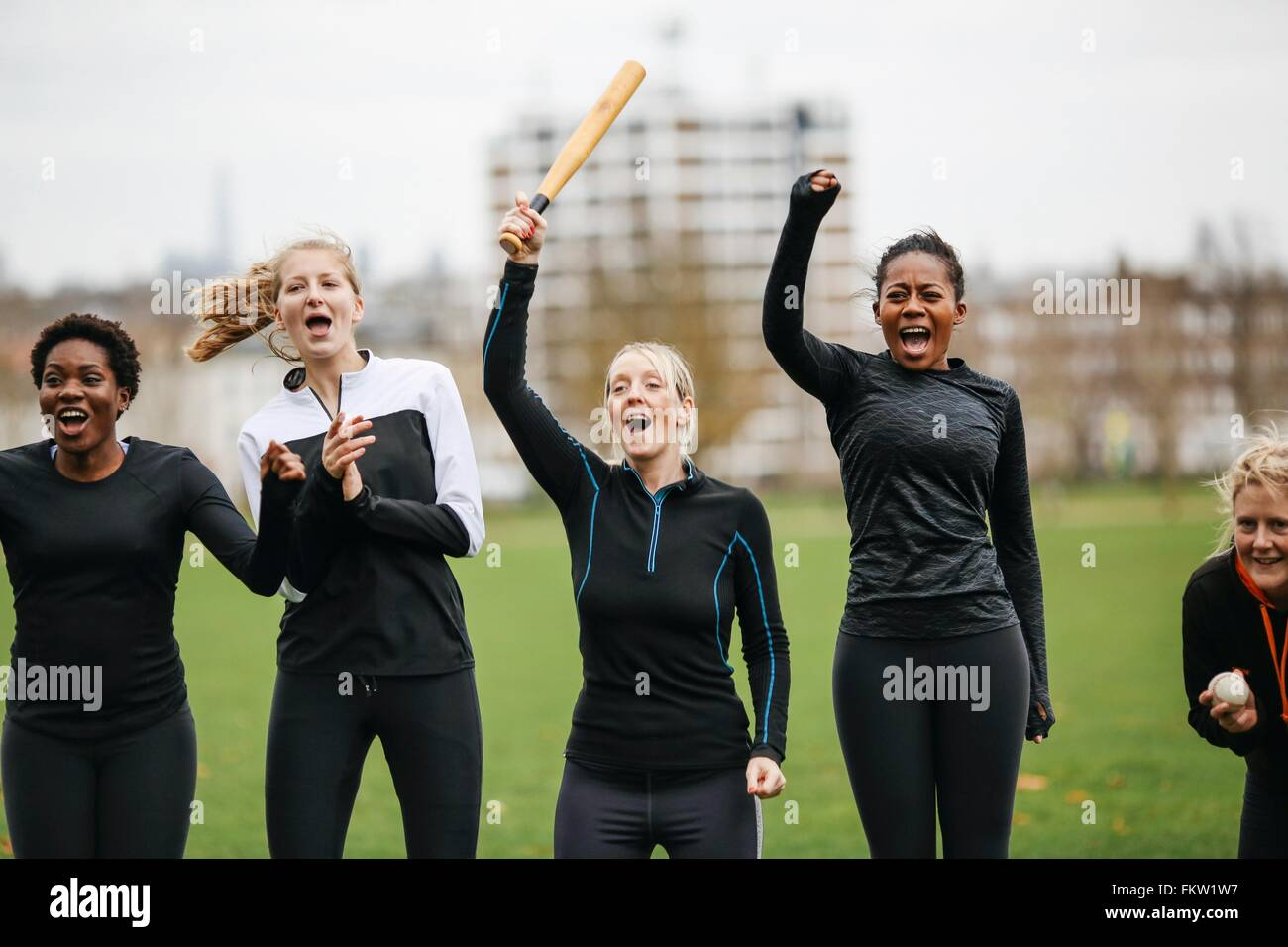 Female rounders team cheering at rounders match - Stock Image