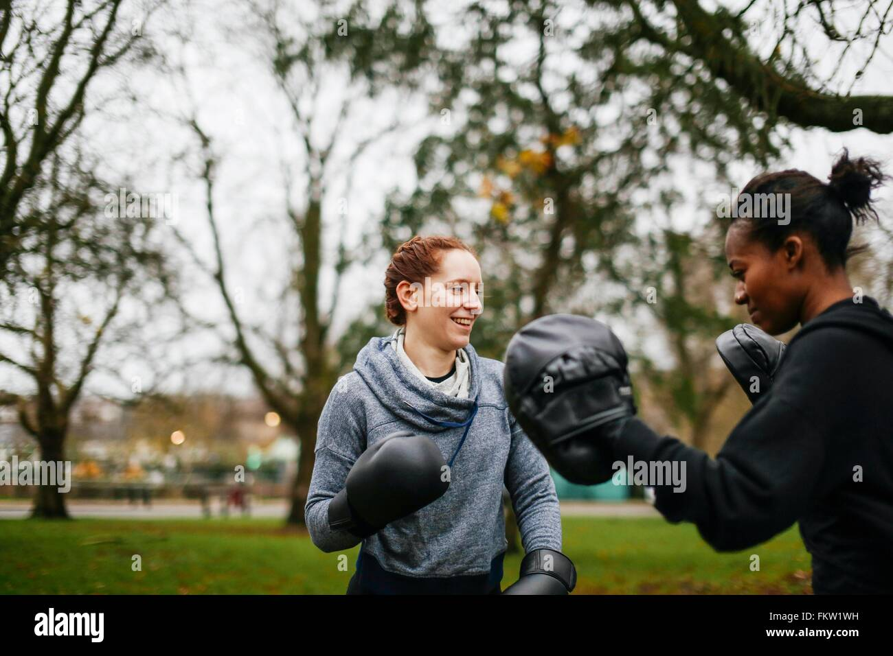 Young adult female boxers training in park - Stock Image