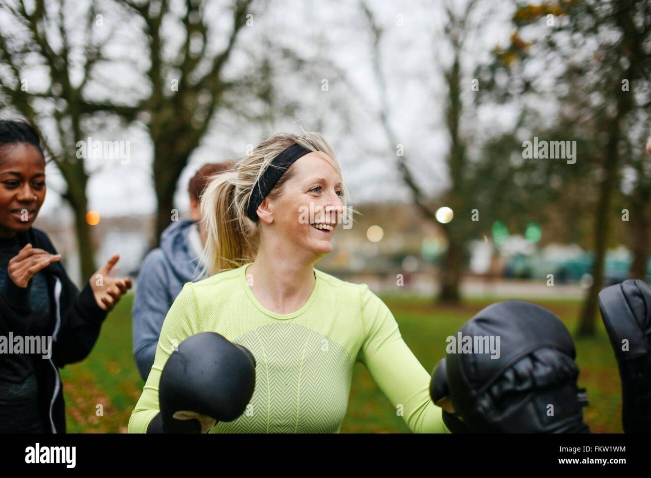 Female boxers wearing boxing gloves training in park - Stock Image