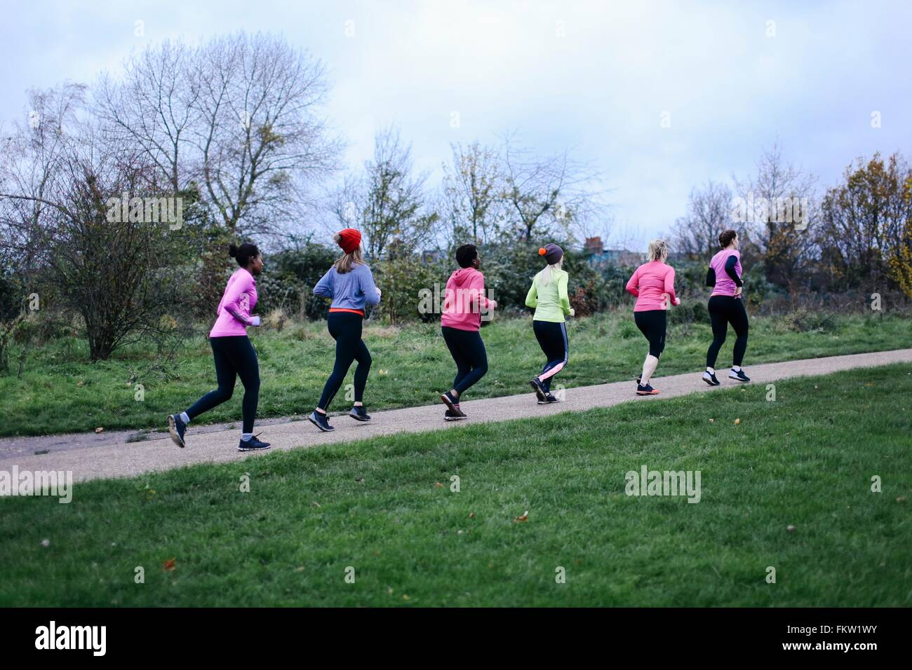 Six adult female runners running on park path Stock Photo