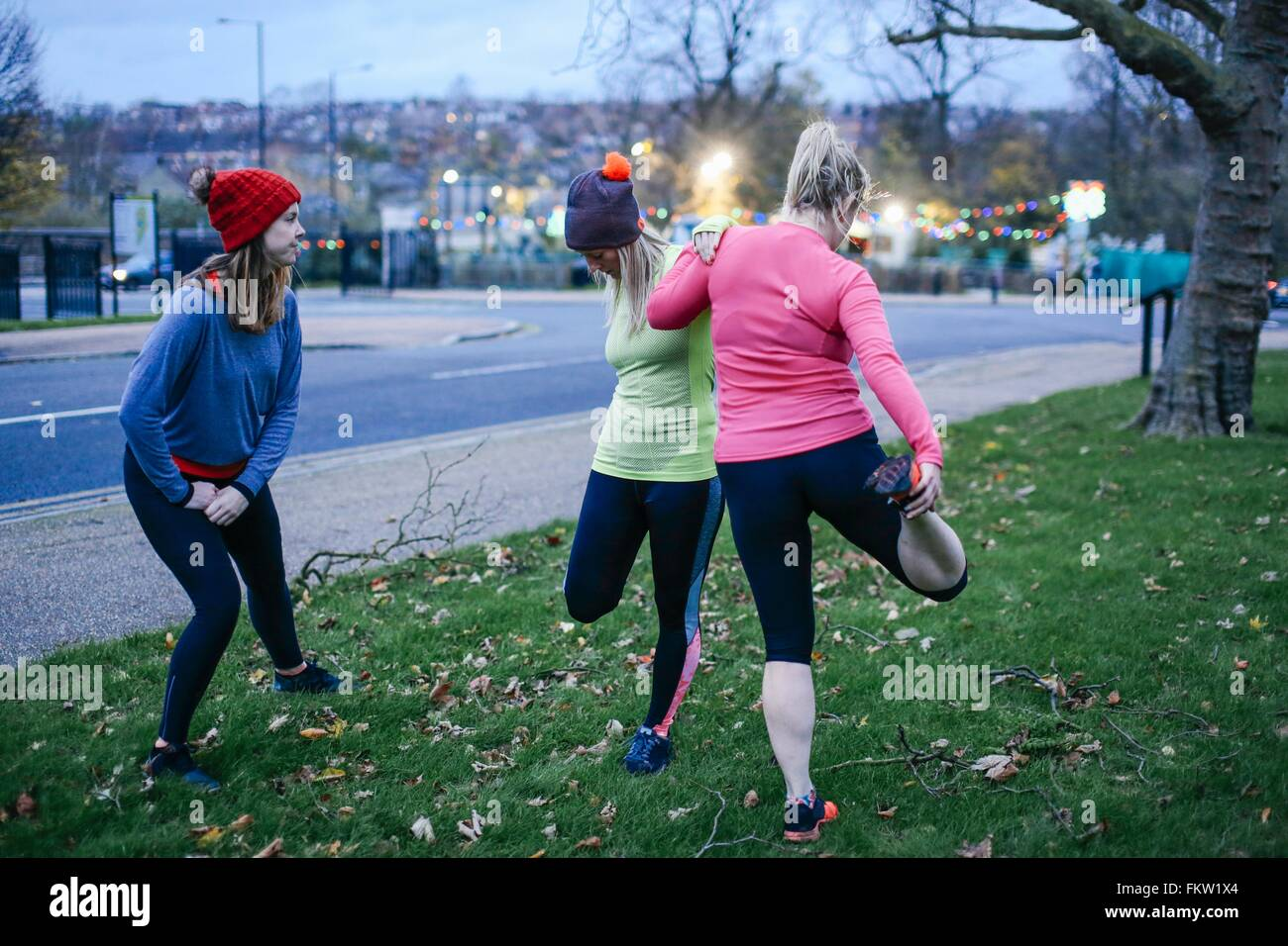 Female runners warming up on city verge at dusk - Stock Image