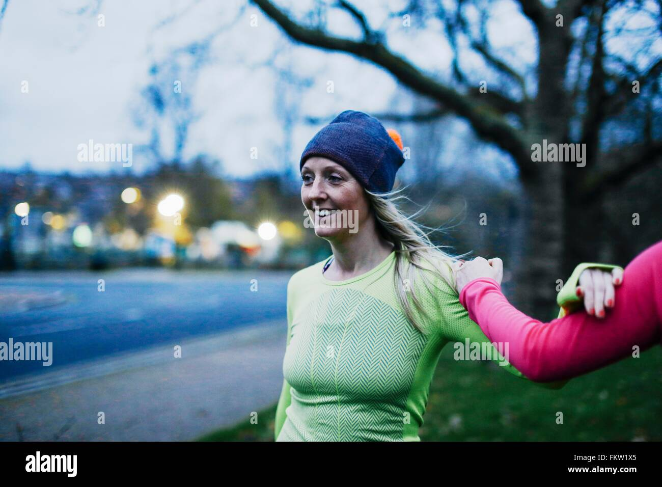 Two adult female runners warming up on city verge at dusk - Stock Image