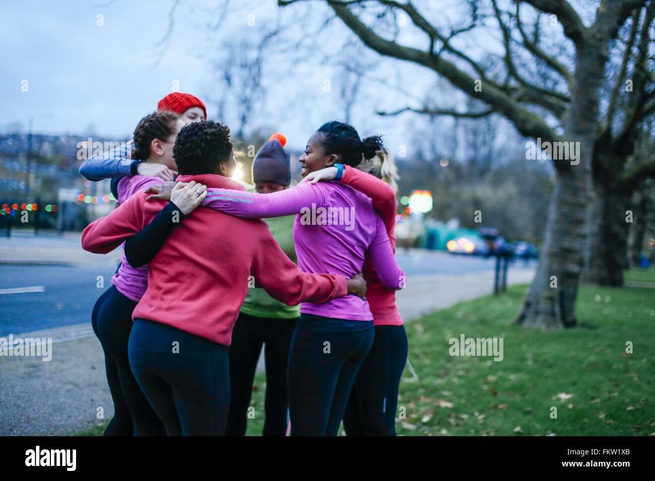 Six female adult runners sharing motivation huddle on city verge at dusk - Stock Image