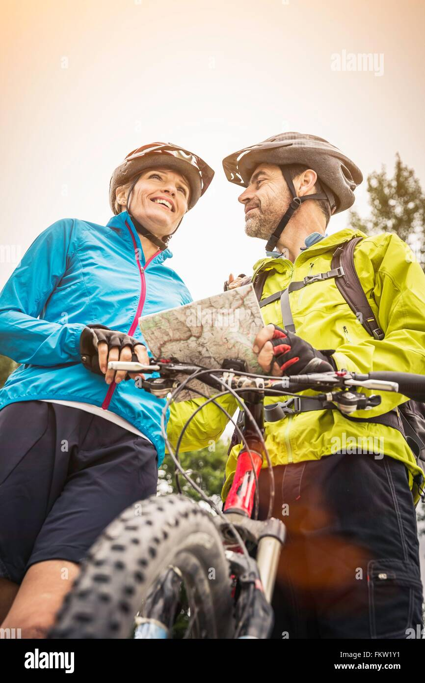 Low angle view of mature mountain biking couple with map - Stock Image