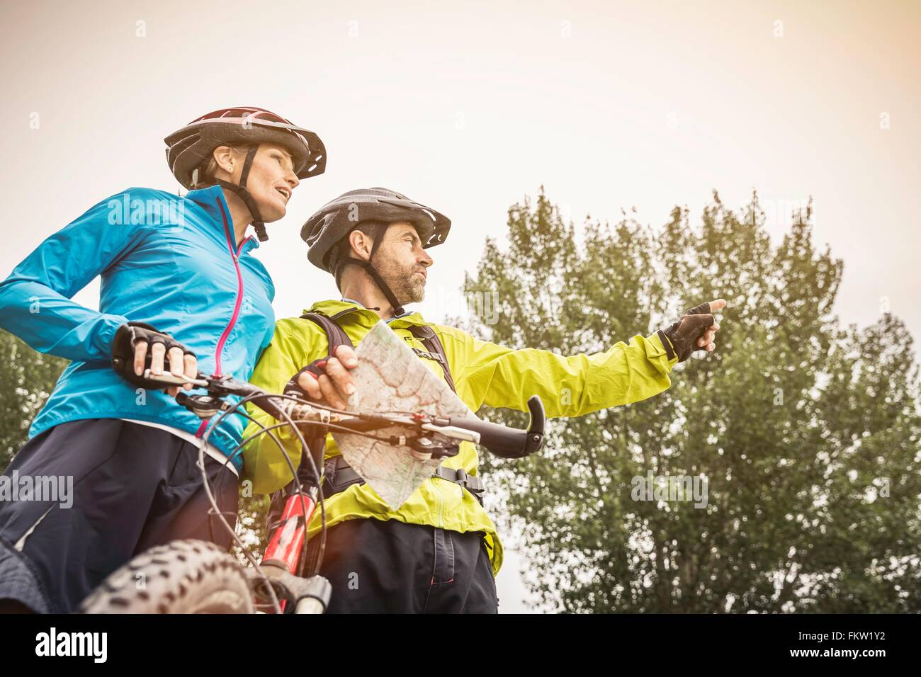 Low angle view of mature mountain biking couple planning with map - Stock Image