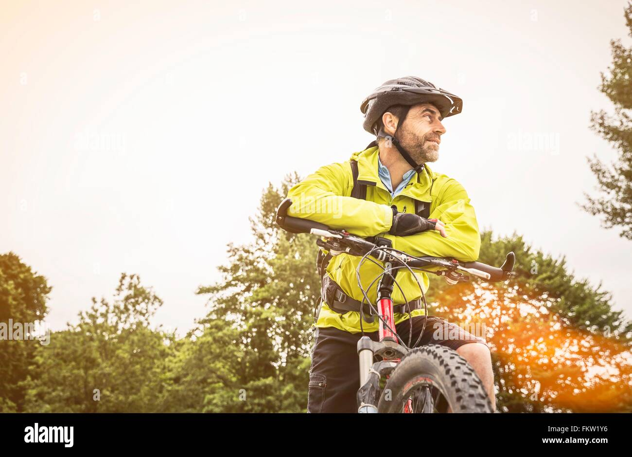 Low angle view of mature male mountain biker taking a break - Stock Image