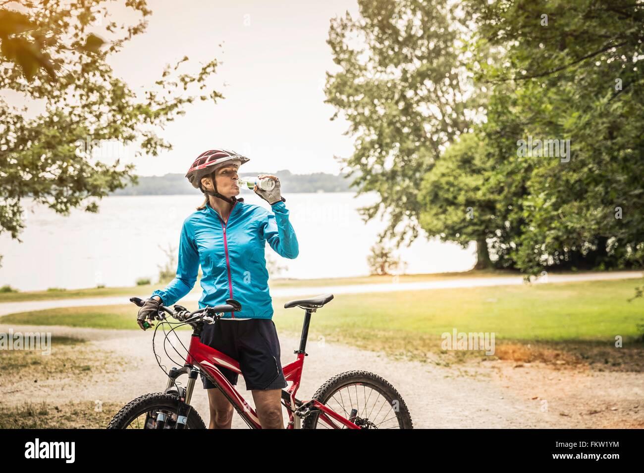 Mature mountain biking woman drinking water at lakeside - Stock Image