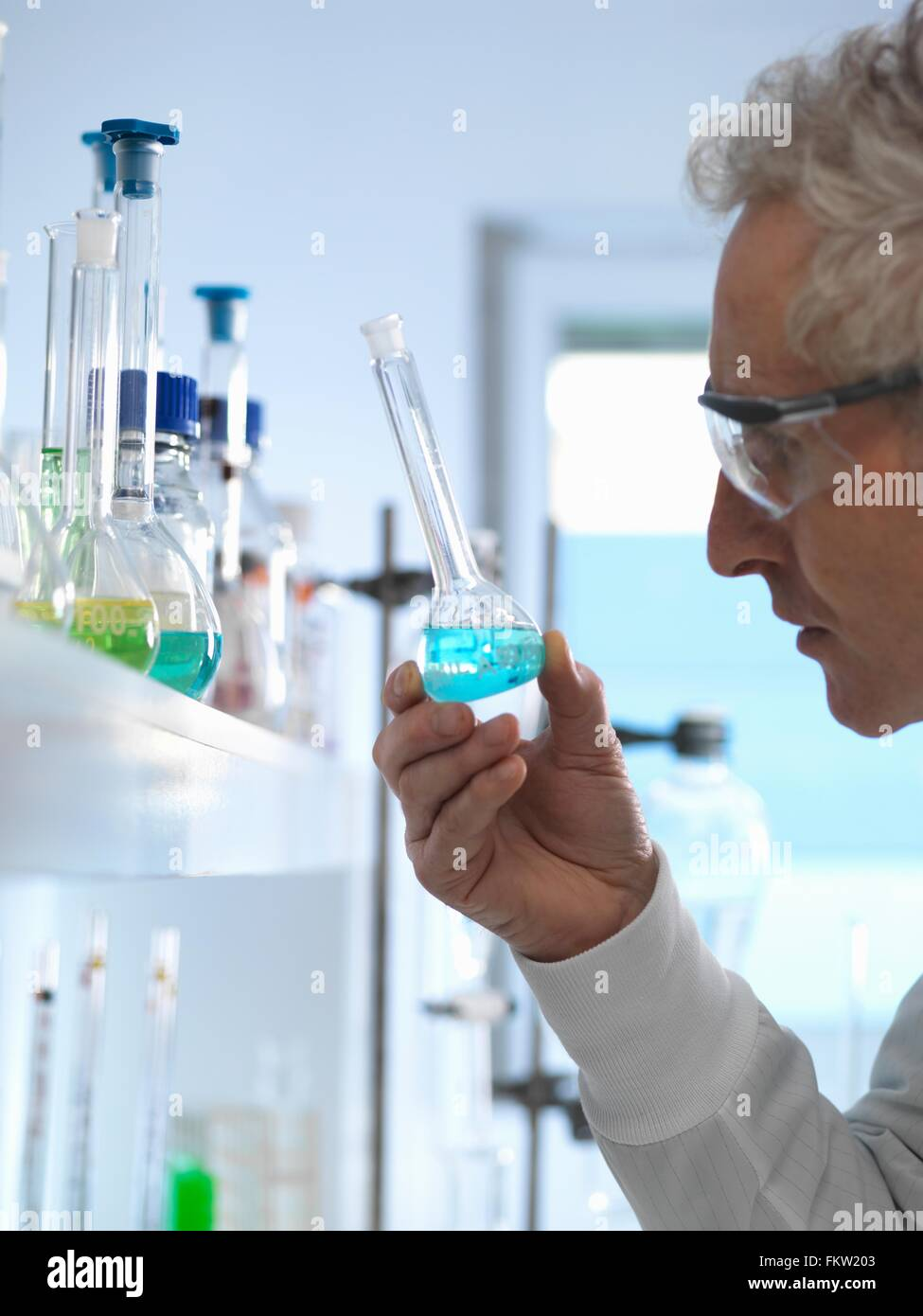 Chemist preparing chemical formula for testing in laboratory - Stock Image