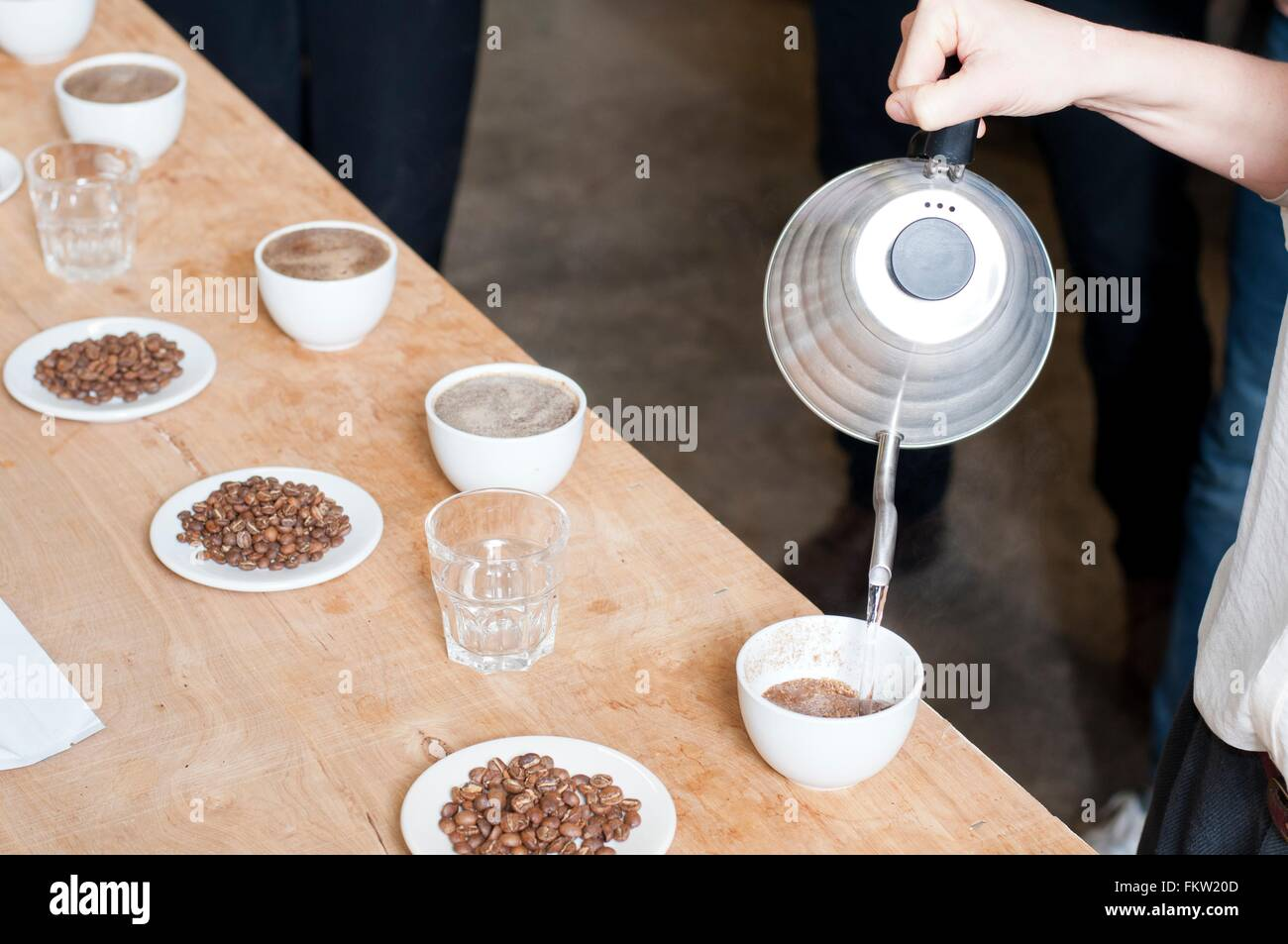 C fee seller pouring hot water into cup   c fee - Stock Image
