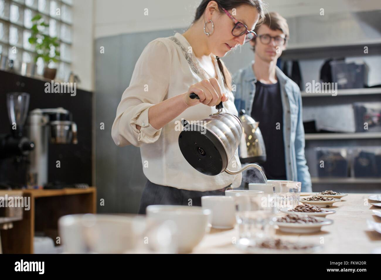 C fee taster pouring hot water into cup   c fee - Stock Image
