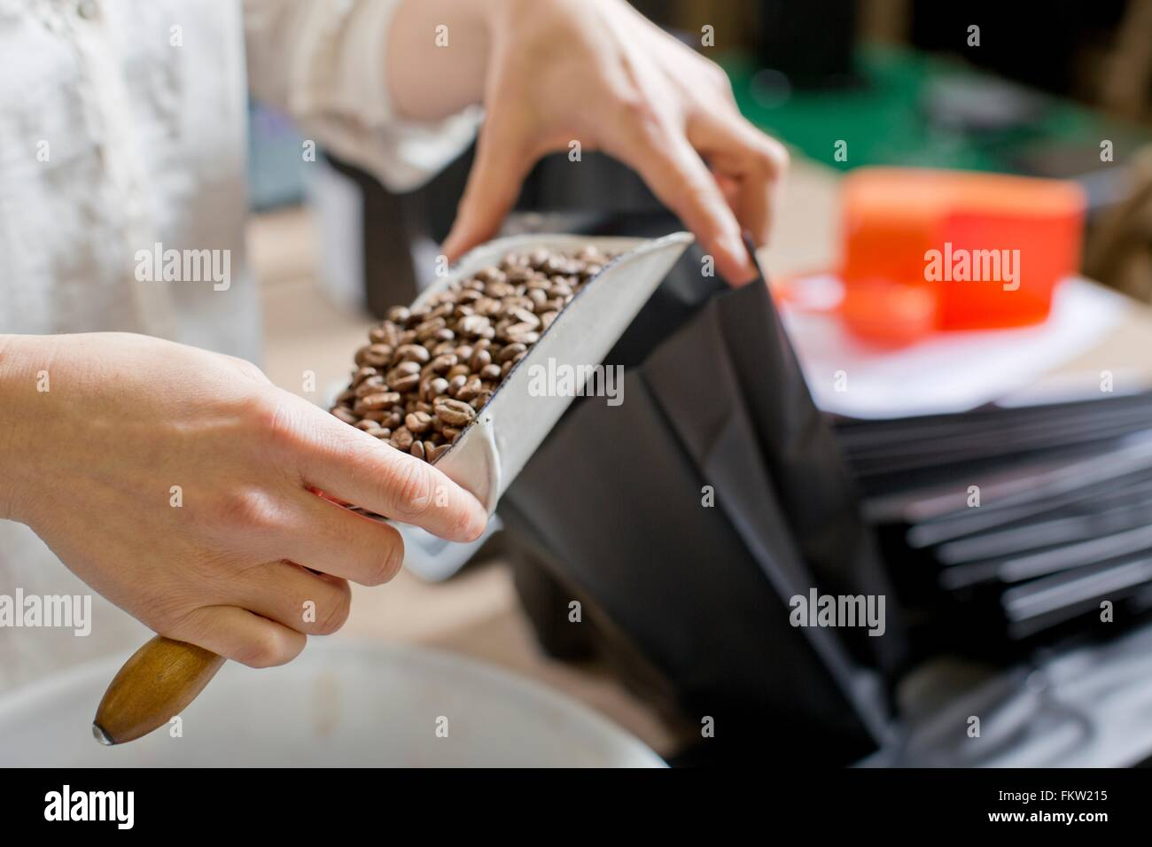 C fee seller filling bag with c fee beans - Stock Image