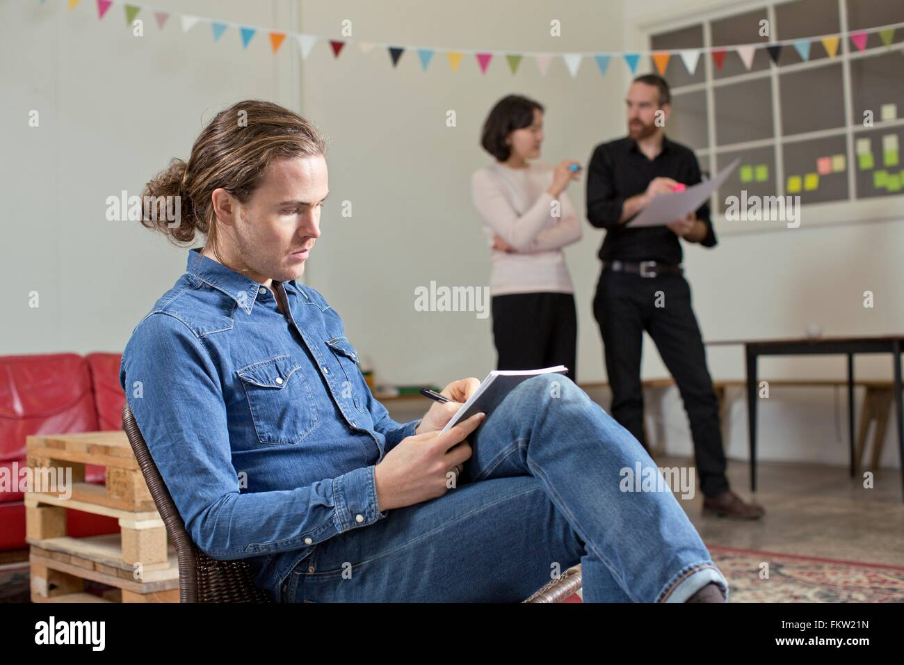Man writing notes, colleagues in background - Stock Image