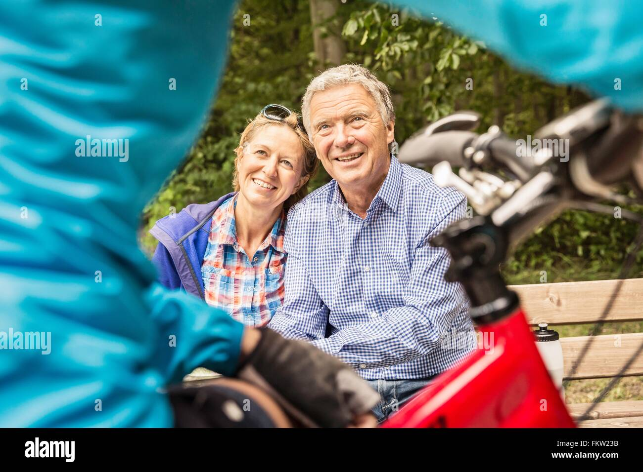 Cropped shot of mountain biker chatting to couple on park bench - Stock Image
