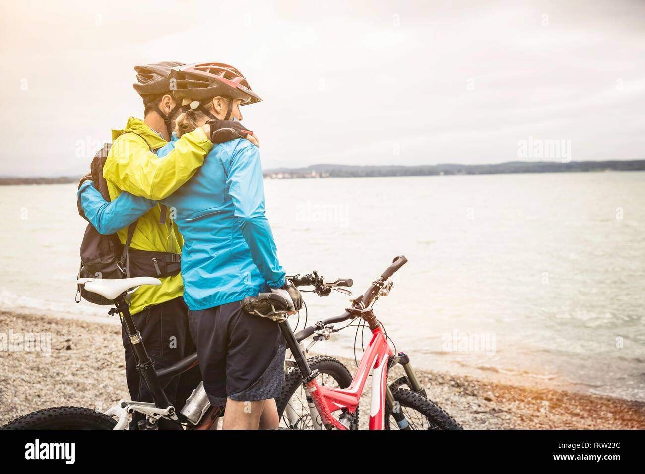 Romantic mountain biking couple looking out from lakeside - Stock Image