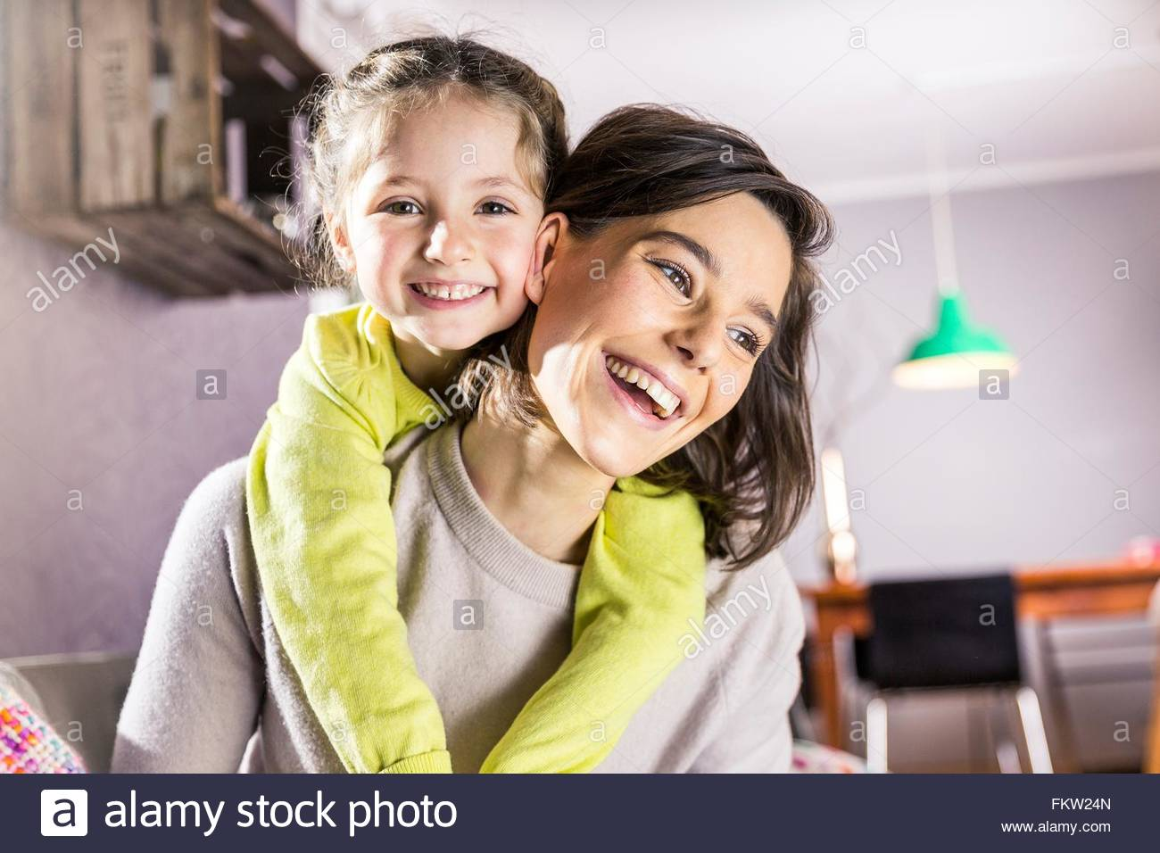 Portrait of girl getting piggyback ride from mother in living room Stock Photo
