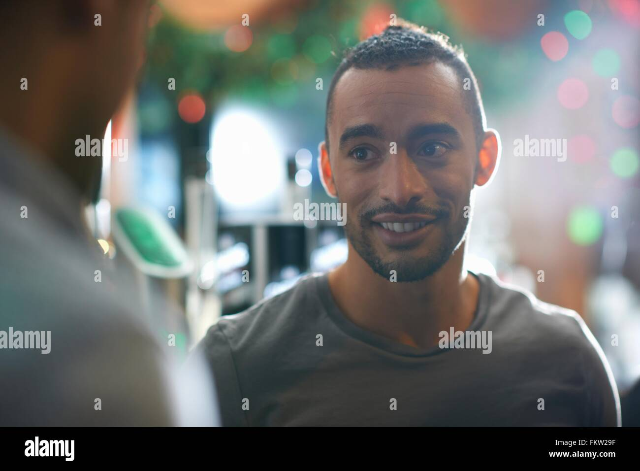 Young man in public house looking away smiling Stock Photo