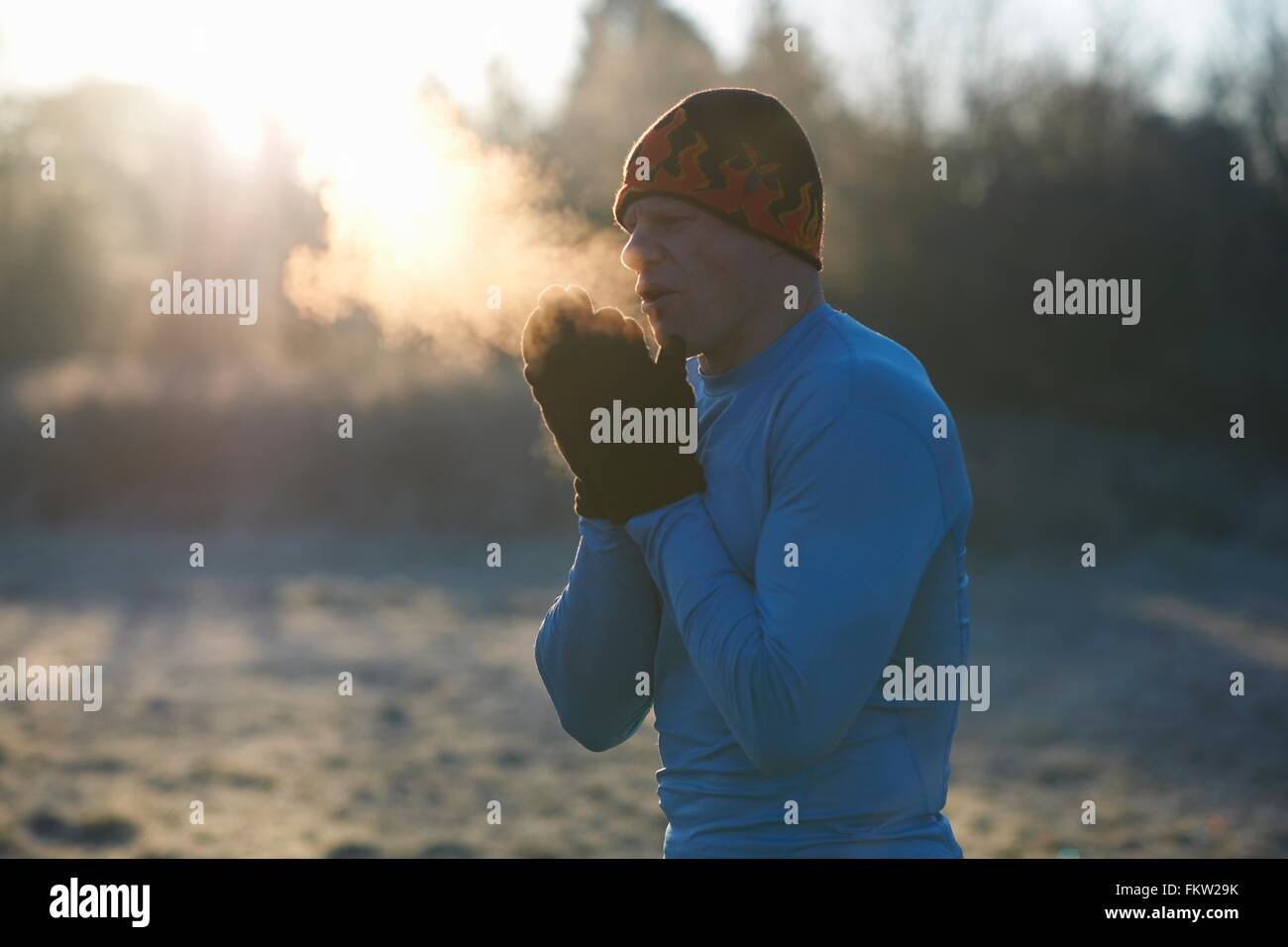 Runner wearing knit hat and gloves, rubbing hands together, breathing cold air - Stock Image