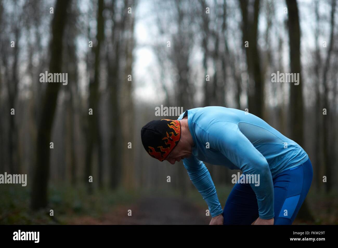 Runner wearing knit hat and spandex bending forward hands on knees exhausted - Stock Image