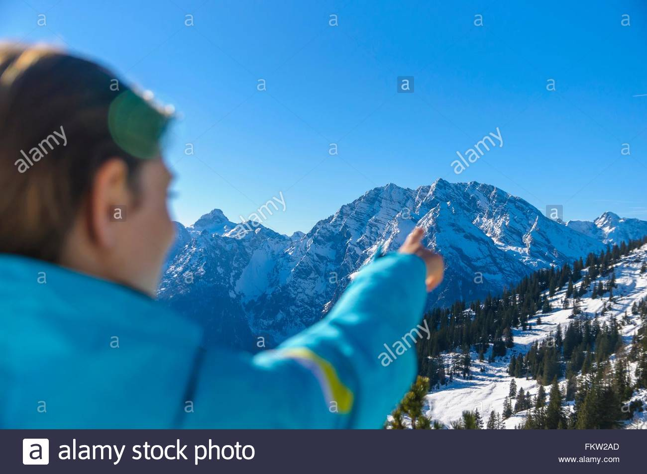 Over the shoulder view of skier pointing at snow capped mountain range, Jenner, Berchtesgadener, Germany - Stock Image