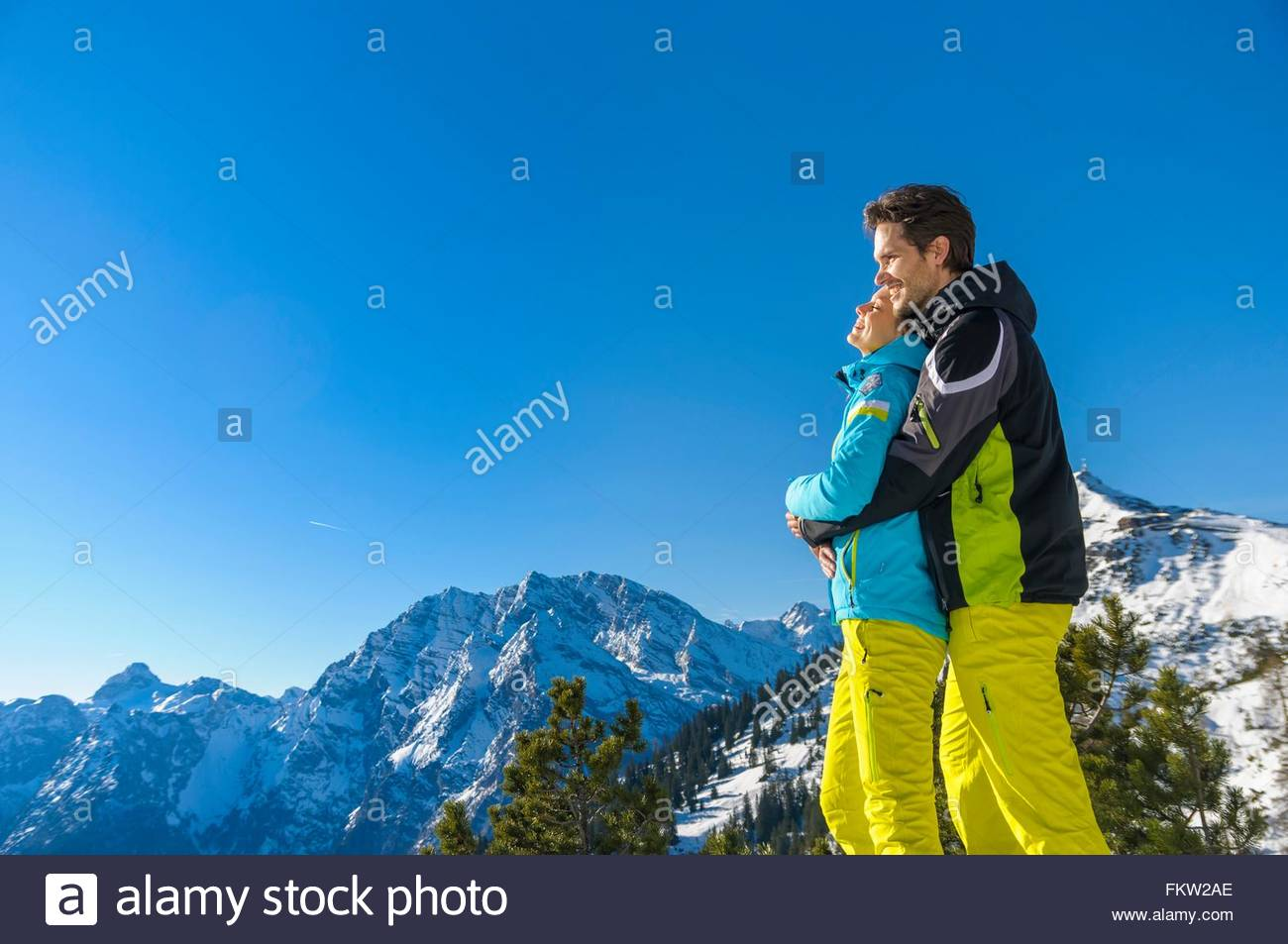 Side view of couple wearing ski suits hugging looking away at view, Jenner, Berchtesgadener, Germany - Stock Image