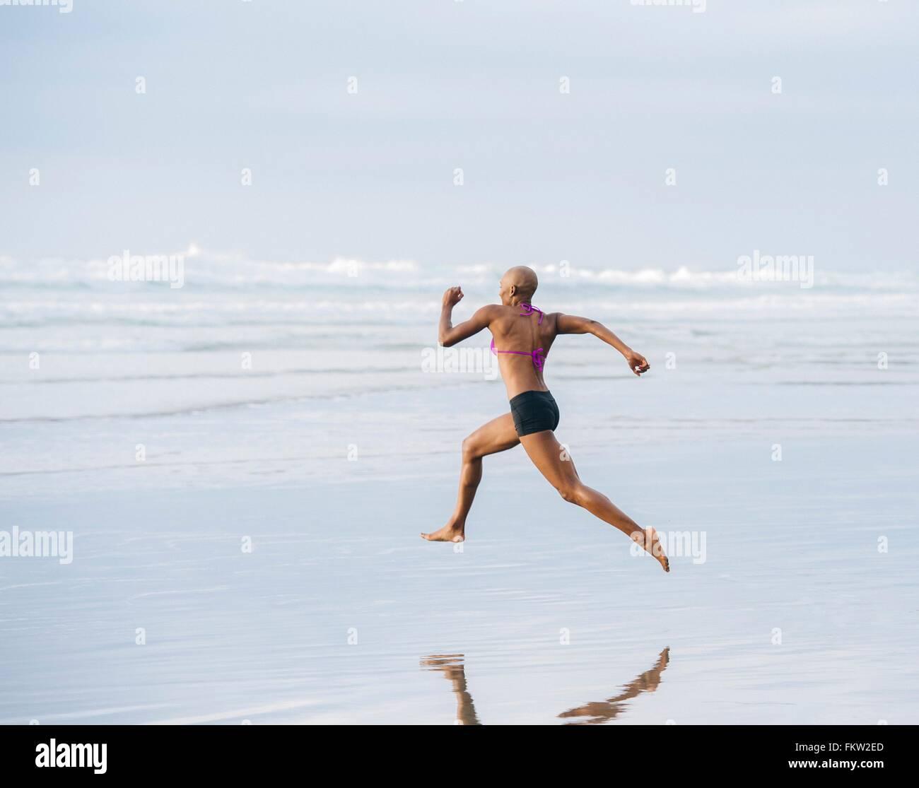 Woman in bikini sprinting on beach - Stock Image