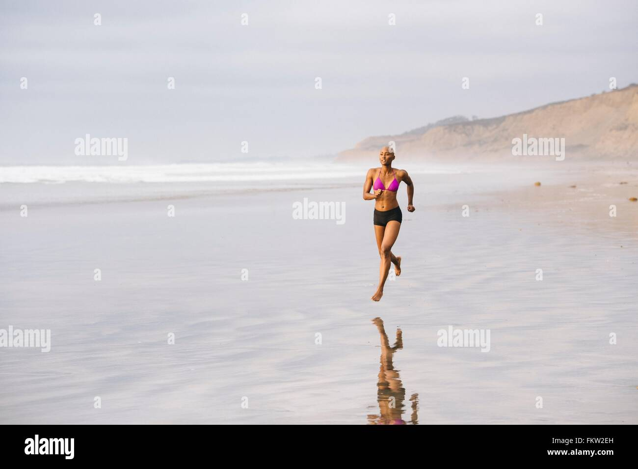 Woman in bikini jogging on beach - Stock Image