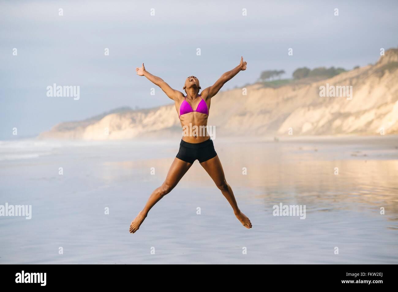 Woman in bikini jumping on beach - Stock Image