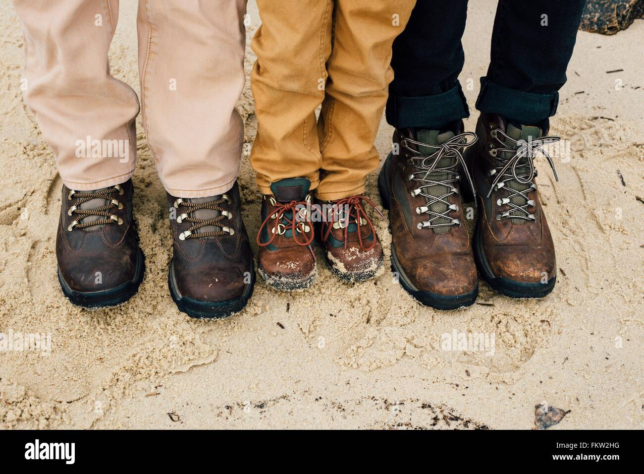 Father standing with two children, focus on feet Stock Photo