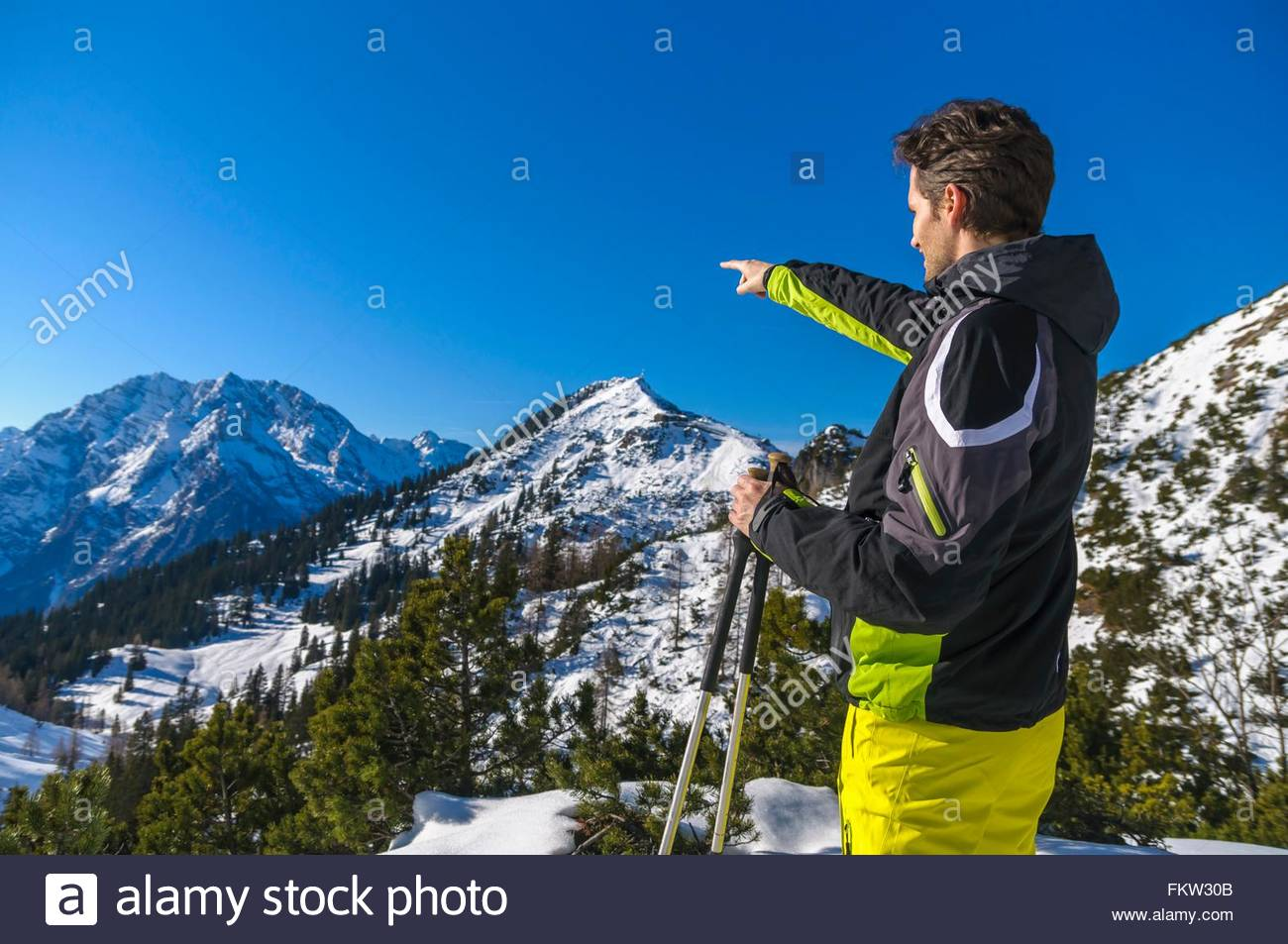 Side view of skier pointing at snow capped mountain range, Jenner, Berchtesgadener, Germany - Stock Image