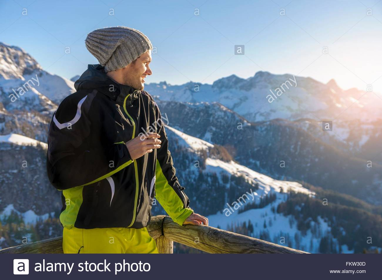 Mid adult man on mountain wearing ski suit and knit hat looking away at view smiling, Jenner, Berchtesgadener, Germany - Stock Image