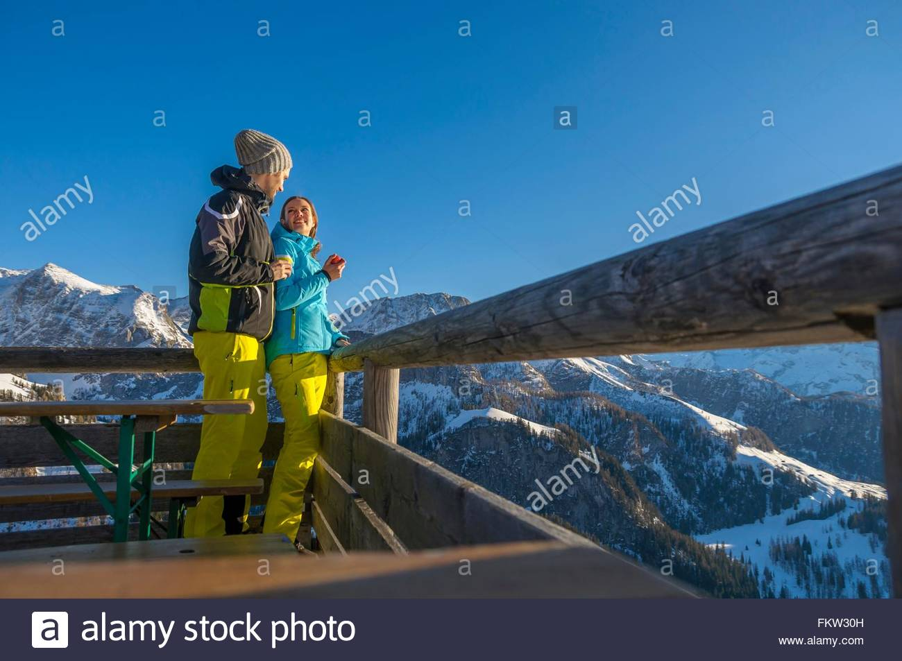 Couple wearing ski suit on viewing platform in mountains smiling, Jenner, Berchtesgadener, Germany - Stock Image