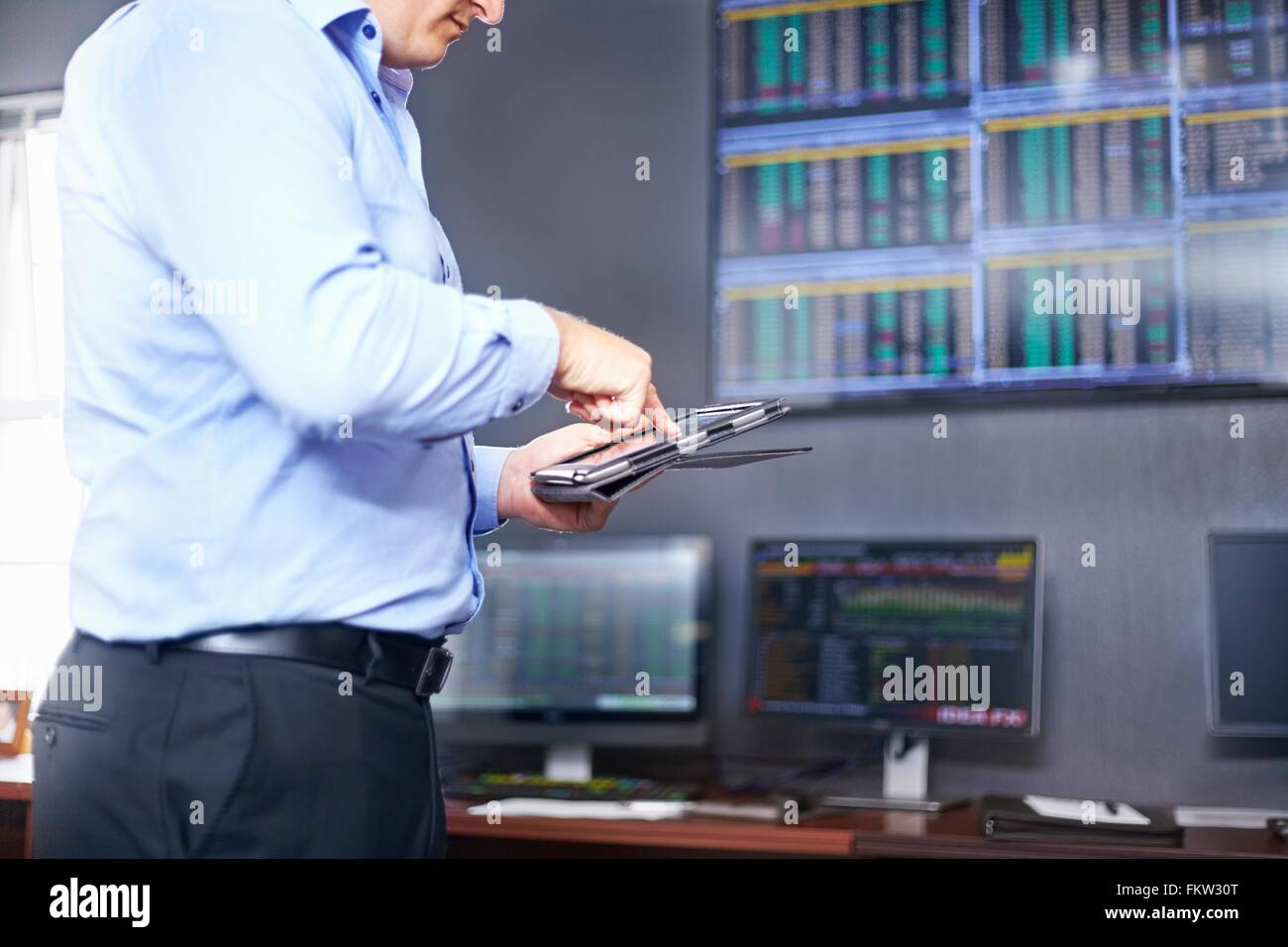 Side view of young mid adult mans mid section in office using digital tablet - Stock Image