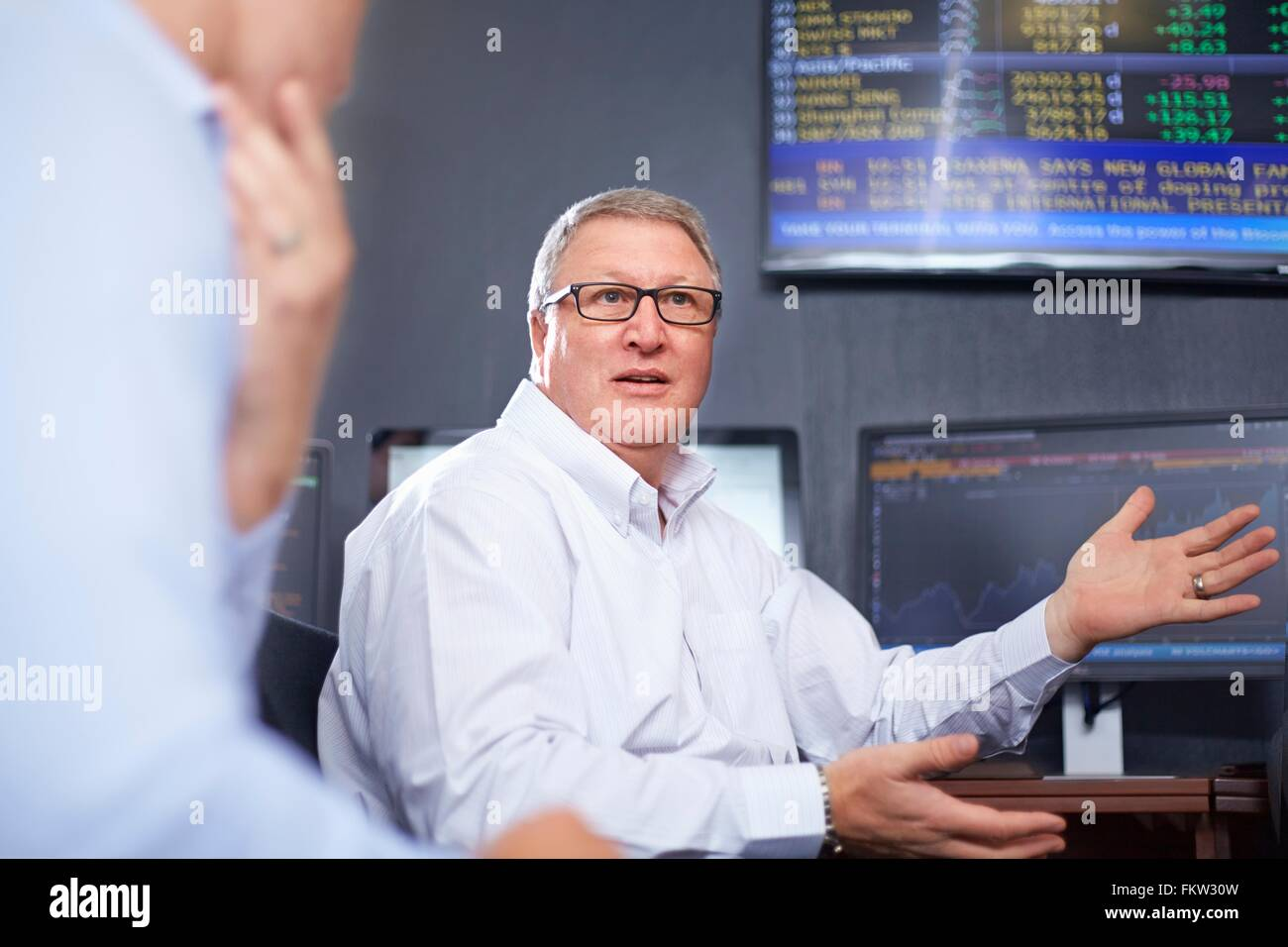 Mature business man in office wearing eye glasses having discussion with colleagues, hand gestures - Stock Image