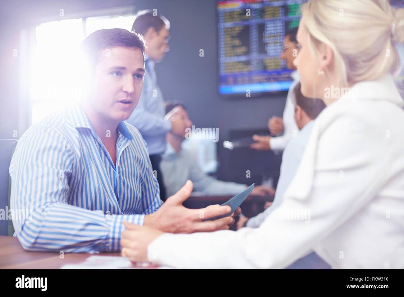 Business man and business woman in  fice face to face having discussion - Stock Image