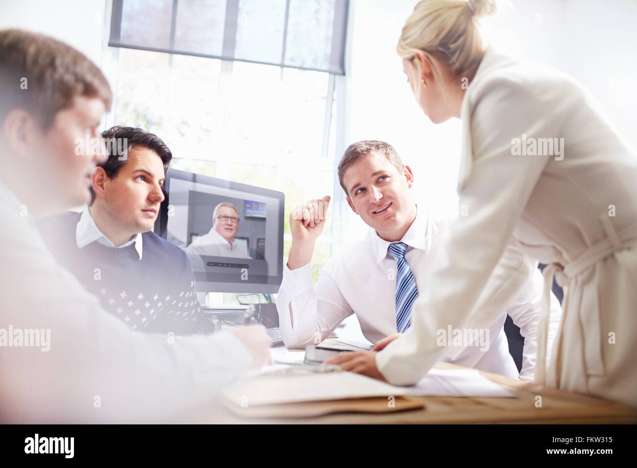 Colleagues in  fice at desk making video call, having discussion - Stock Image